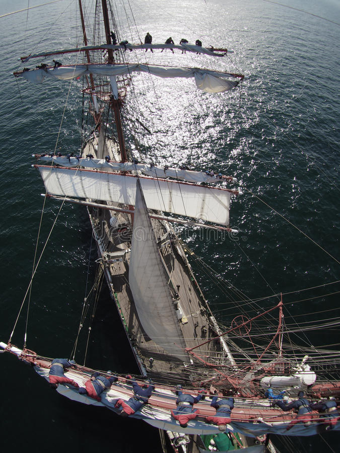 Sailors working aloft in a huge tallship, crazy perspective. Sailors furling sails aloft in a tallship royalty free stock images