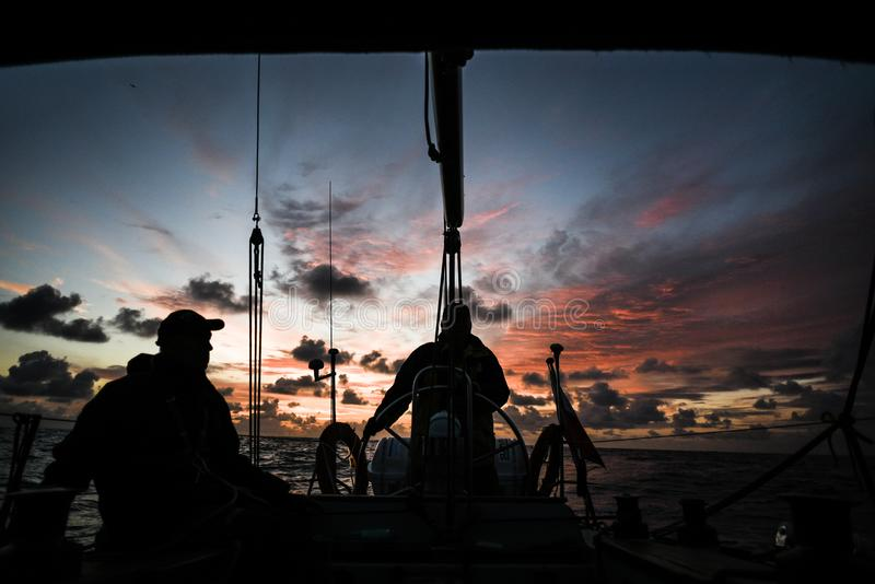 Sailors on a yacht during sunset over the North Sea stock photo