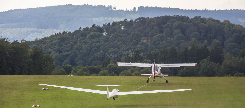 Sailplane en een slepend vliegtuig die op een vliegveld beginnen stock afbeelding