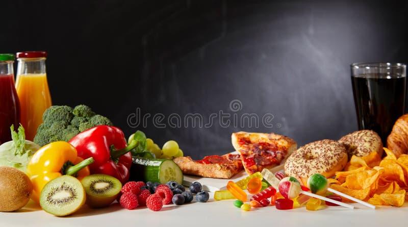Sain contre les nourritures malsaines avec l'espace de copie photos stock