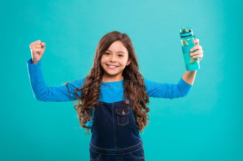 Sain et hydraté Soins de fille au sujet de santé et d'équilibre d'eau Fond bleu de bouteille d'eau gaie de prise de fille gosse photo stock