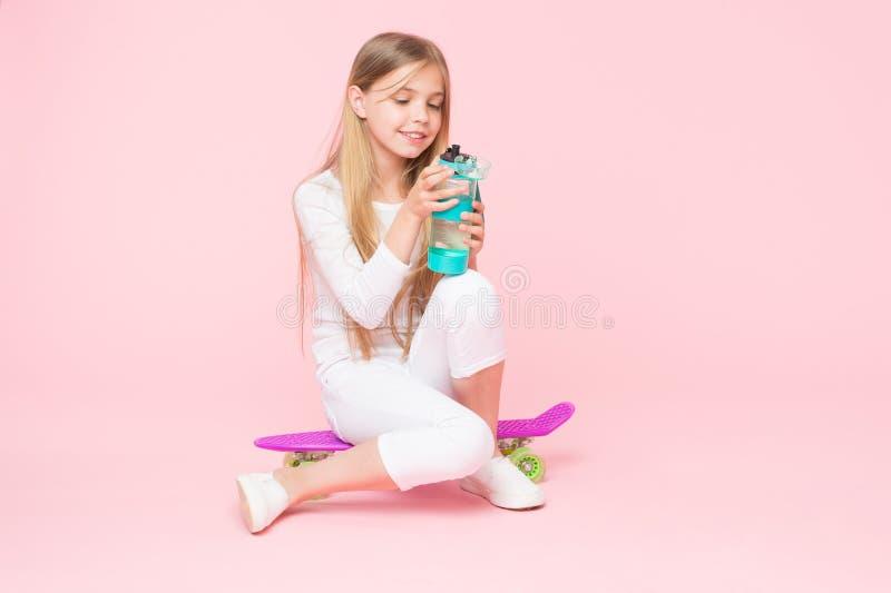 Sain et vivant Petit patineur de fille maintenant hydraté avec des habitudes saines Petit enfant actif buvant assez d'eau pour image stock