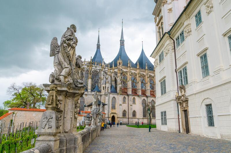 Saint Barbara`s Cathedral Roman Catholic church Gothic style building. And baroque statues in front of Jesuit College in Kutna Hora historical Town Centre stock images