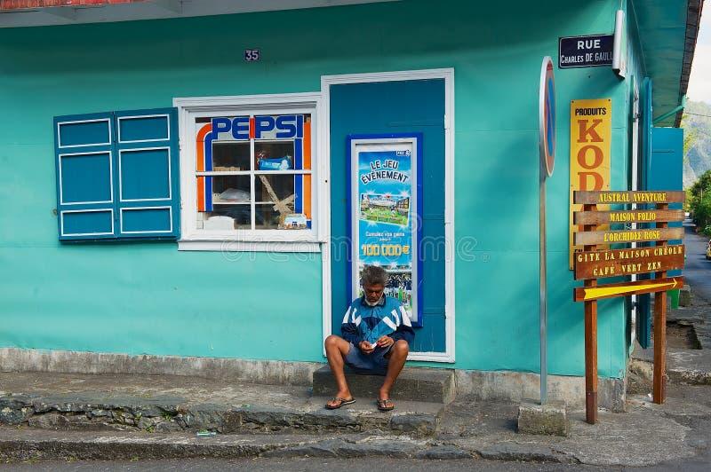 Senior man sits next to the mini market shop entrance in Fond de Rond Point in Saint-Denis De La Reunion, France. stock image