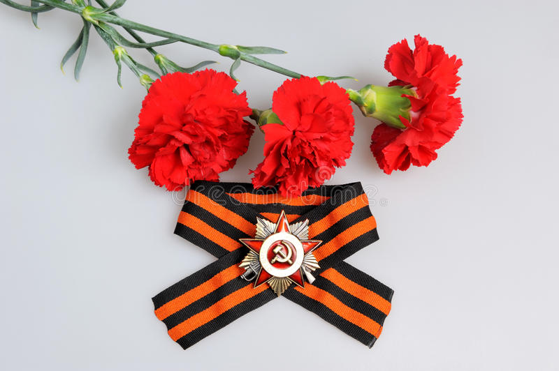 Saint George ribbon with order of Great Patriotic and red carnations on gray stock photos