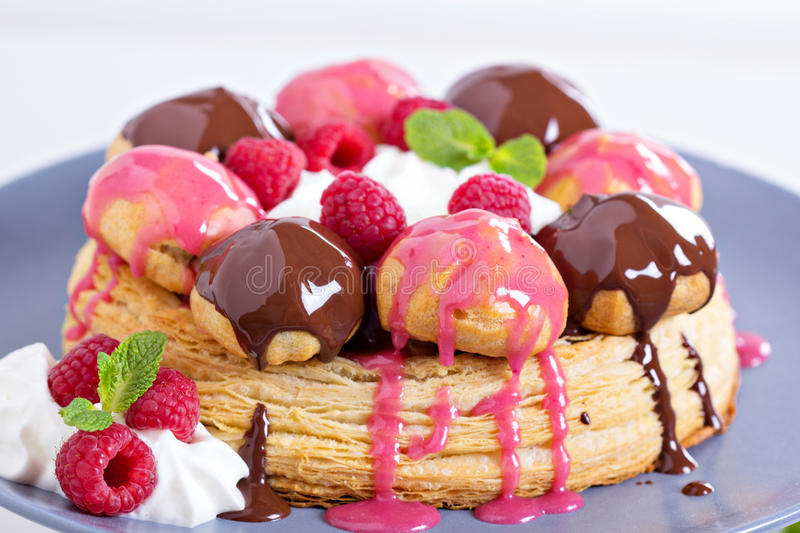 Saint-Honore cake with chocolate and raspberry. Saint-Honore cake with whipped cream, chocolate and raspberry royalty free stock photo
