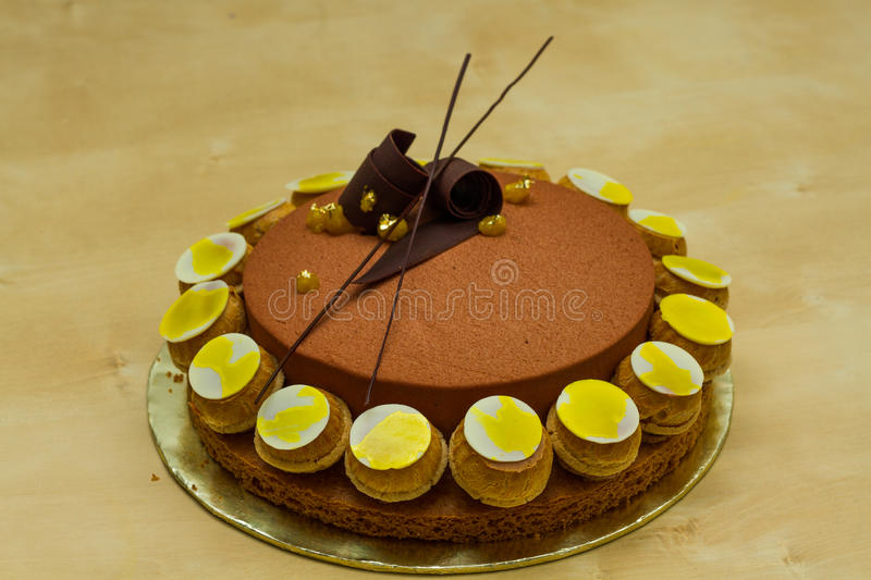 Saint honore. Homemade saint honore with chocolate mouse , passion fruits jelly , choux pastry ,chocolate deco, gold leaf stock images