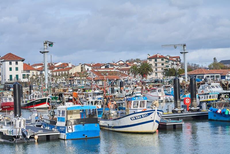 Saint Jean de Luz, França; 03-18-2019 aqui a arquitetura popular colorida encontra os barcos imagem de stock