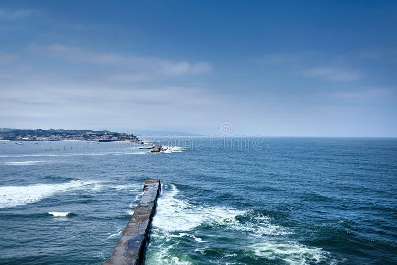 Saint Jean de Luz, France. Basque country. City views Ciboure and Castle and port of Socoa. Ocean waves breaking about the dam royalty free stock image