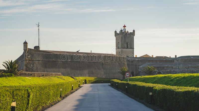 Saint Julian Fortress entrance with green garden, Oeiras, Lisbon. Saint Julian Fortress Forte de Sao Juliao da Barra entrance with green garden, tower, and stock photos