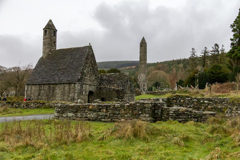 Saint Kevin`s Kitchen and the Round Tower at the Glendalough Monastic Site in Wicklow, Ireland royalty free stock images