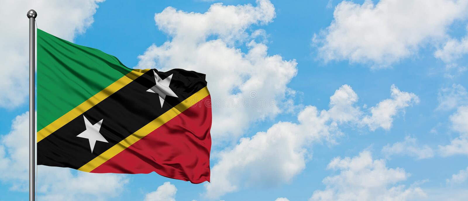 Saint Kitts And Nevis flag waving in the wind against white cloudy blue sky. Diplomacy concept, international relations.  stock photography