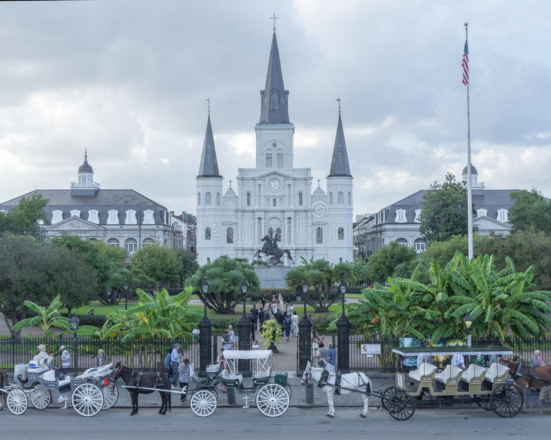 Saint Louis Cathedral, New Orleans. NEW ORLEANS, USA - OCTOBER 10, 2014: Horse-drawn carriages are lined up along the street and a wedding party take pictures in stock images