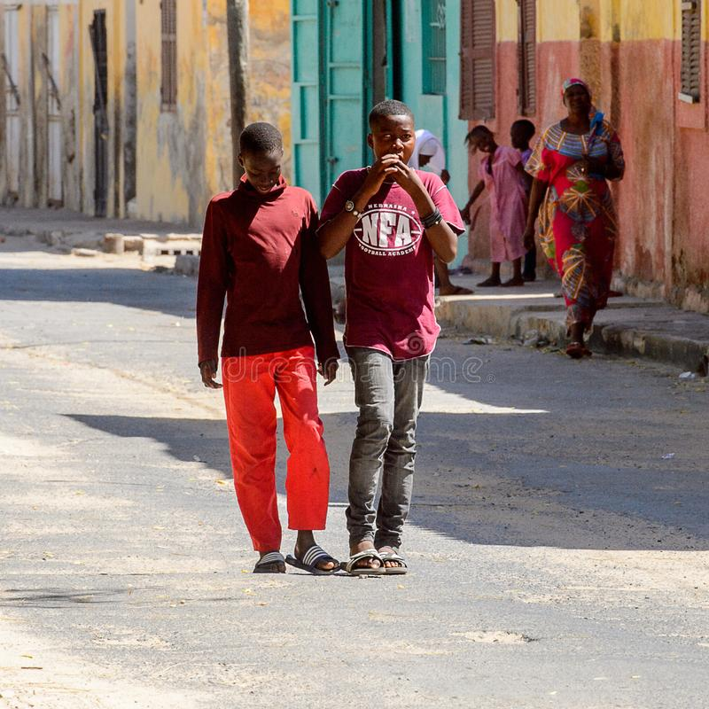 Unidentified Senegalese boys walk along the street with colored. SAINT LOUIS, SENEGAL - APR 24, 2017: Unidentified Senegalese boys walk along the street with stock photo