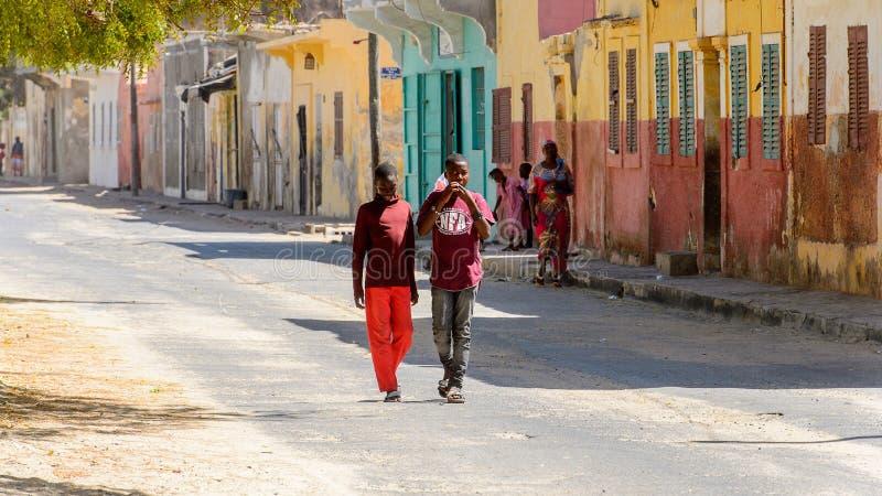 Unidentified Senegalese boys walk along the street with colored. SAINT LOUIS, SENEGAL - APR 24, 2017: Unidentified Senegalese boys walk along the street with stock photos