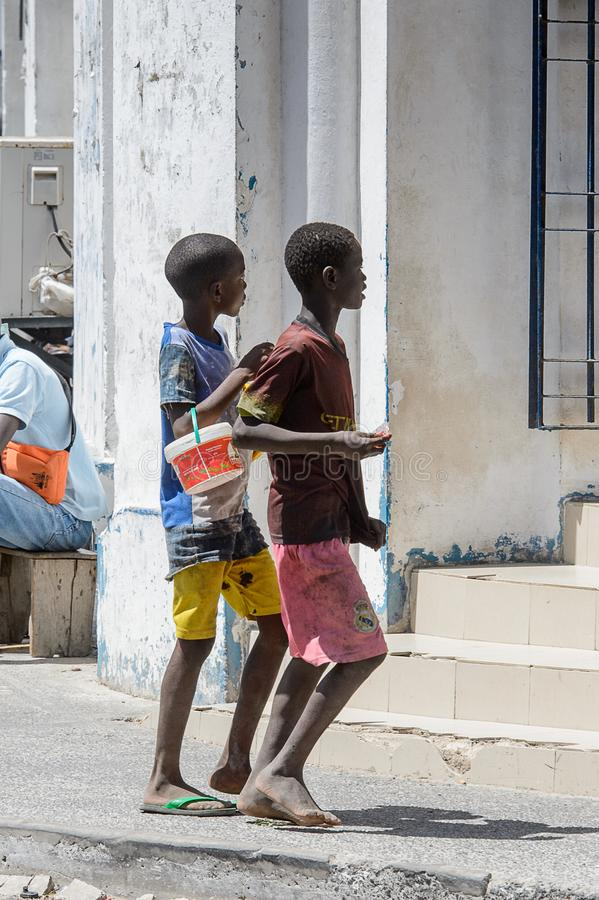 Unidentified Senegalese two boys walk along the street in the c. SAINT LOUIS, SENEGAL - APR 24, 2017: Unidentified Senegalese two boys walk along the street in royalty free stock images