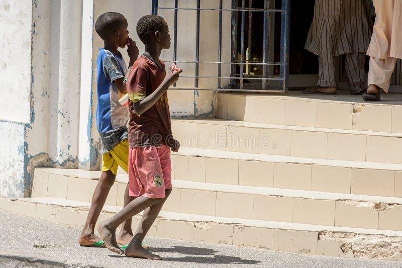 Unidentified Senegalese two boys walk along the street in the c. SAINT LOUIS, SENEGAL - APR 24, 2017: Unidentified Senegalese two boys walk along the street in stock photo