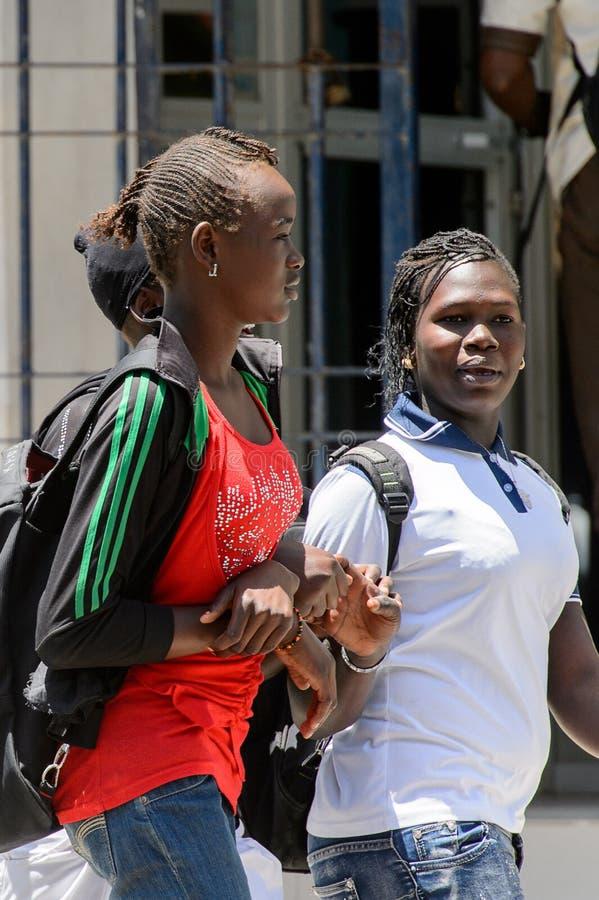 Unidentified Senegalese women walk along the street in the cent. SAINT LOUIS, SENEGAL - APR 24, 2017: Unidentified Senegalese women walk along the street in the stock photo