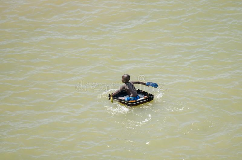 Saint-Louis, Senegal - October 20, 2013: Unidentified African boy using suitcase as boat and paddling with sandals.  royalty free stock image