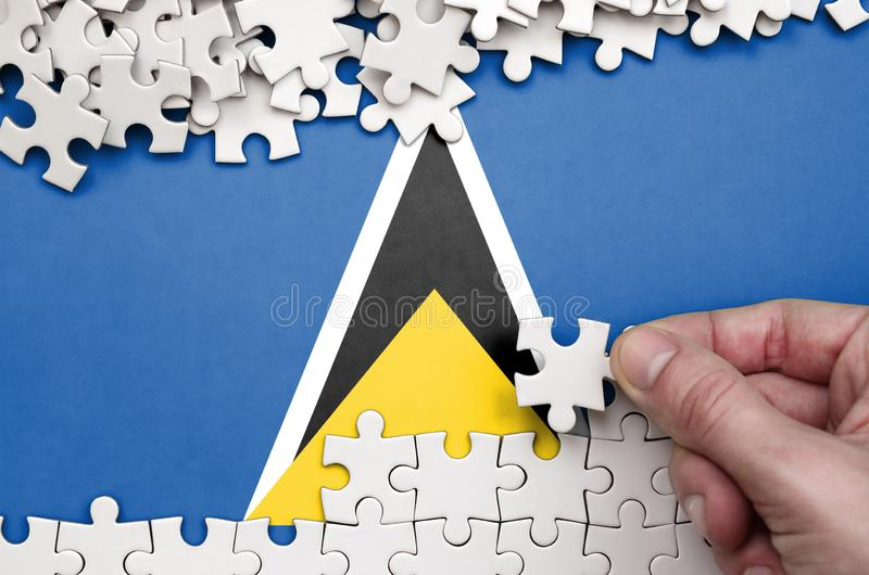 Saint Lucia flag is depicted on a table on which the human hand folds a puzzle of white color royalty free stock photo