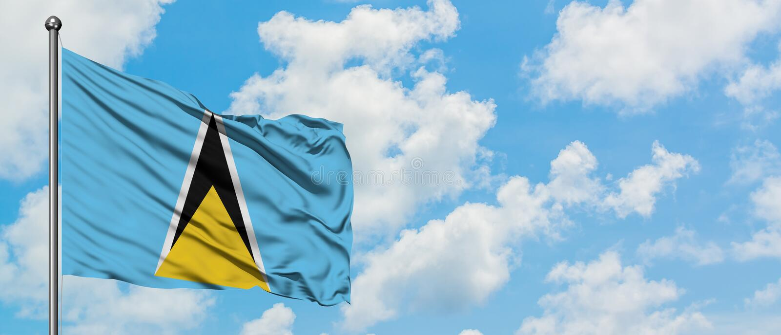 Saint Lucia flag waving in the wind against white cloudy blue sky. Diplomacy concept, international relations.  royalty free stock image