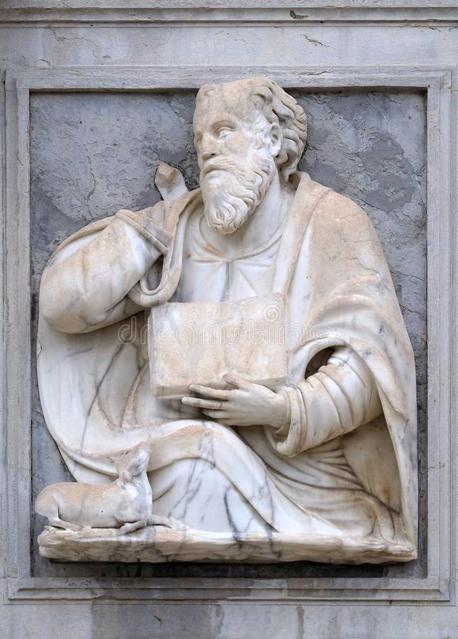 Saint Luke the Evangelist. Relief on the portal of the Cathedral of Saint Lawrence in Lugano, Switzerland stock photos