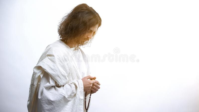 Saint man praying with Rosary, light falling as sign of forgiveness, salvation. Stock photo stock image