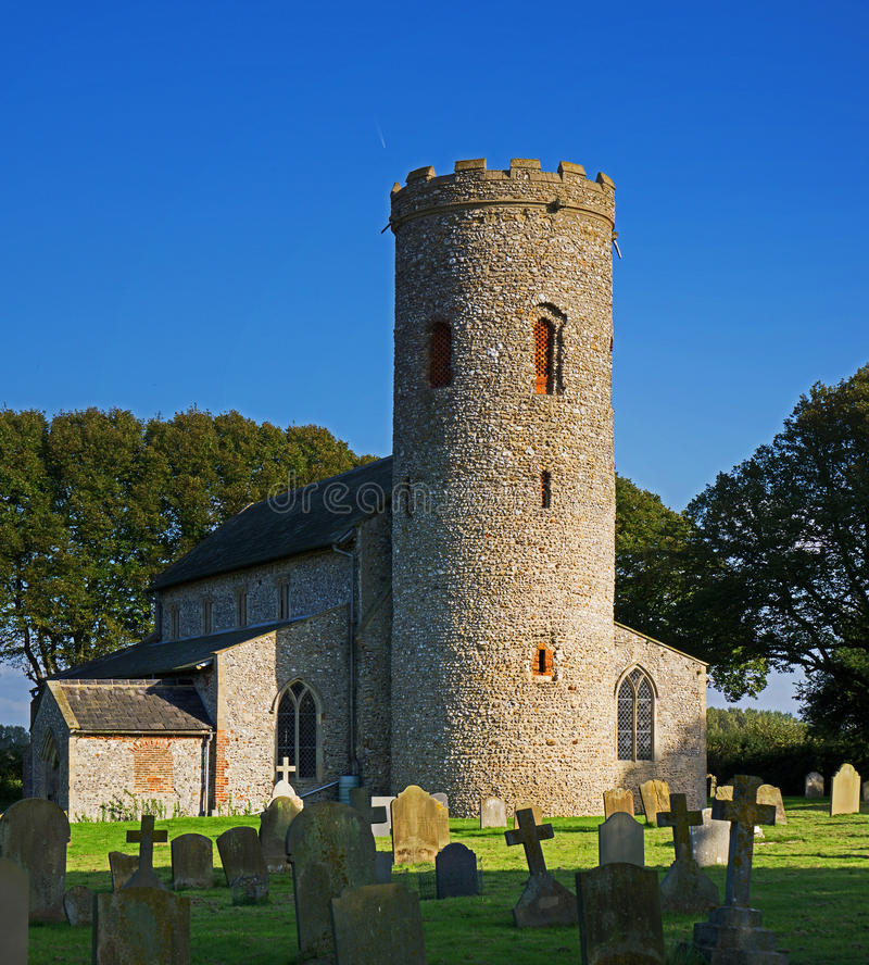 Saint Margarets Church with round tower. The church and graveyard of the round towered flint church of Saint Margarets,Burham Overy,Norfolk,UK royalty free stock images