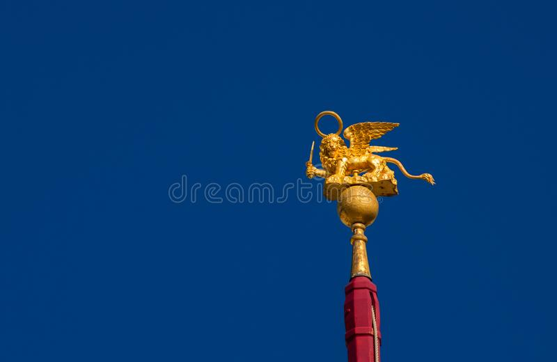 Saint Mark Lion in Venice. Saint Mark Winged Lion golden statuette wielding a sword against blue sky, a symbol of the Old Venice Republic at war with copy space stock images
