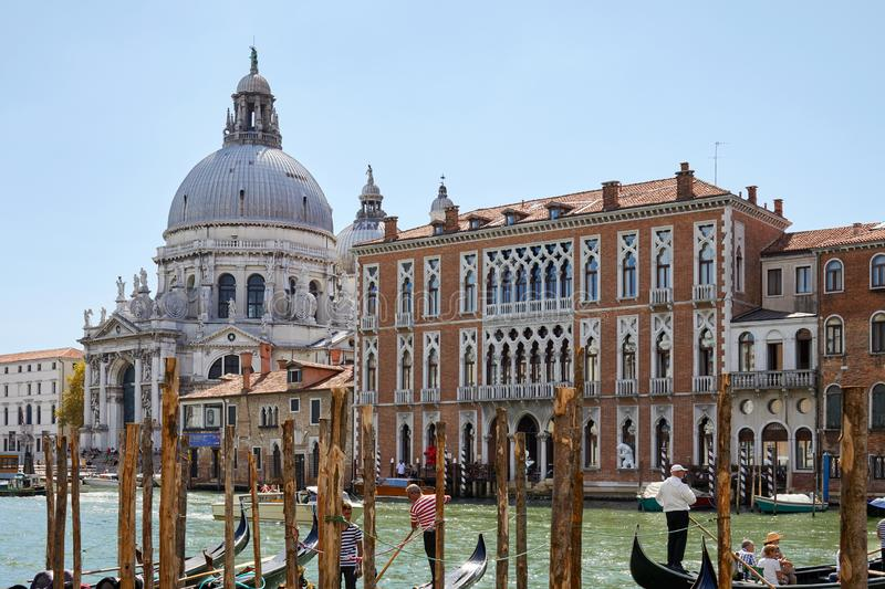 Saint Mary of Health basilica and gondolas with people and tourists in Venice royalty free stock photo