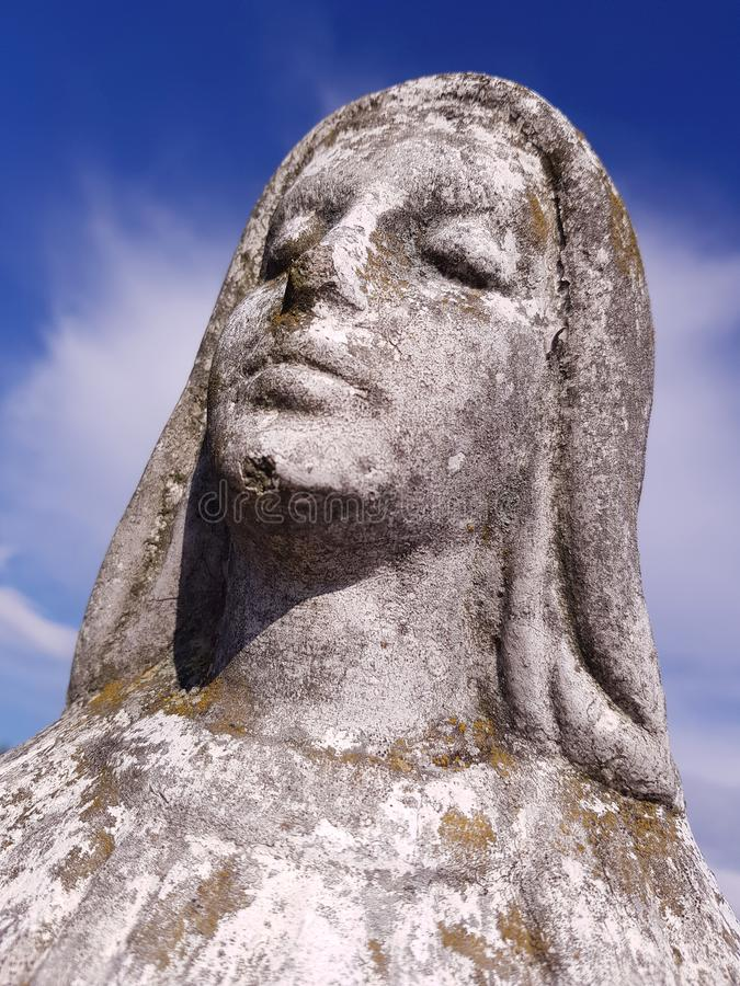Saint Mary mossy sculpture closeup, cloudy sky as a background royalty free stock photography