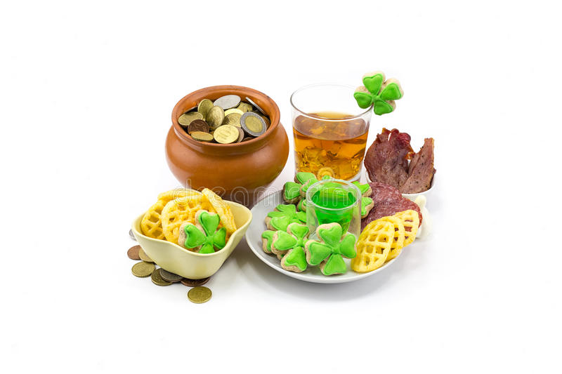 Saint Patrick's Day Scotch whiskey glass ice extraction pot of gold coins and clover snack plate of meat and biscuits stock image