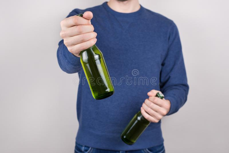Saint Patrick day concept. Cropped close-up photo of drunk handsome positive guy holding bottle of tasty fresh beer in hand stock photos