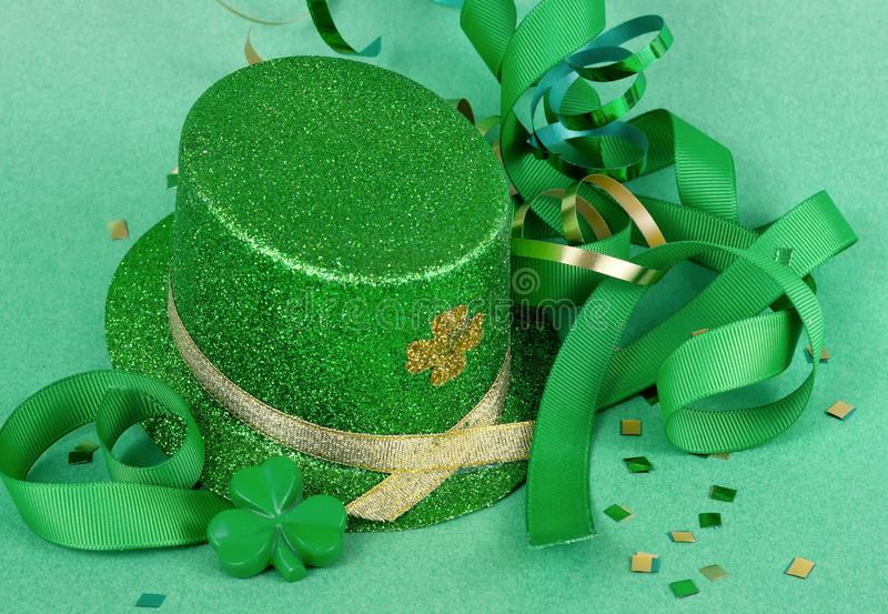 Saint Patrick`s Day image of sparkly green and gold leprechaun hat with curls of green and gold ribbon on a green background with stock photography