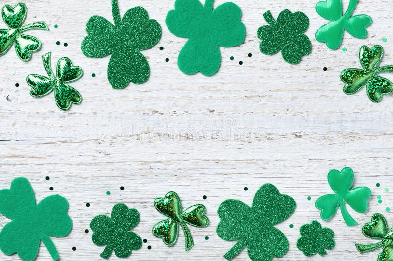 Saint Patricks Day border with green shamrock on white rustic board top view. royalty free stock images
