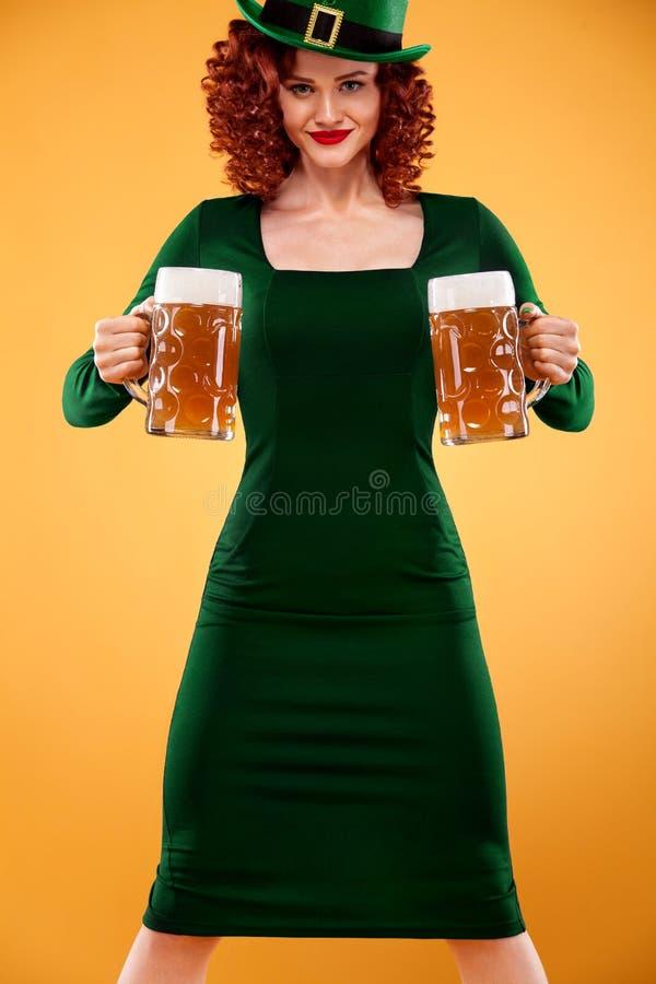 Saint Patricks Day. Young ginger Oktoberfest leprechaun, wearing green dress and hat, serving big beer mugs on orange royalty free stock photo