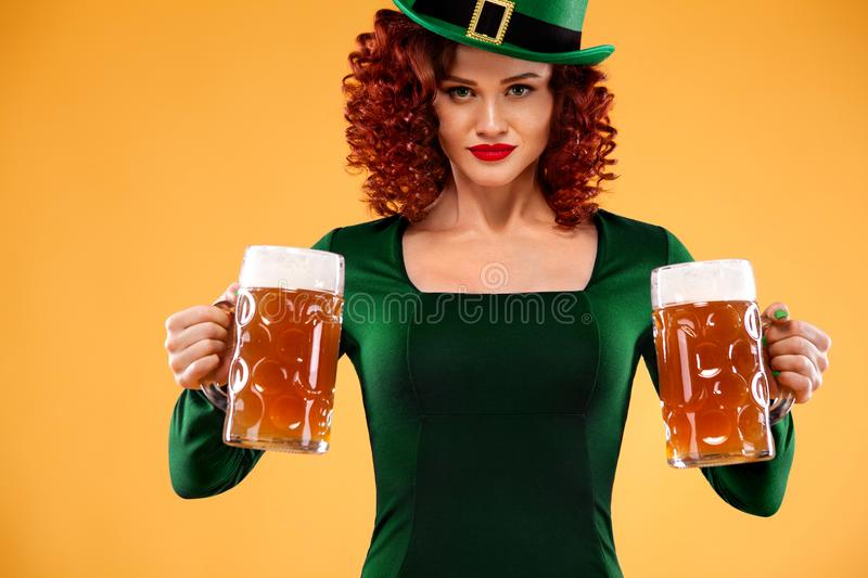 Saint Patricks Day. Young ginger Oktoberfest leprechaun, wearing green dress and hat, serving big beer mugs on orange stock photography