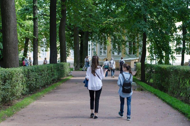 SAINT- PETERSBURG, ROSJA - 20 sierpnia 2016: Peterhof Dwie dziewczyny idące po parku fotografia stock