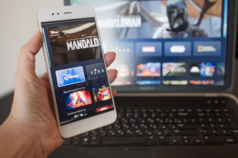 SAINT PETERSBURG, RUSSIA - APRIL 12, 2019: New service from Disney, movies and TV series by subscription. To the streaming platform. Phone in hand, illustrative stock photography