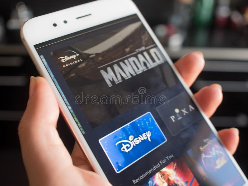 SAINT PETERSBURG, RUSSIA - APRIL 12, 2019: New service from Disney, movies and TV series by subscription. To the streaming platform. Phone in hand, illustrative royalty free stock image