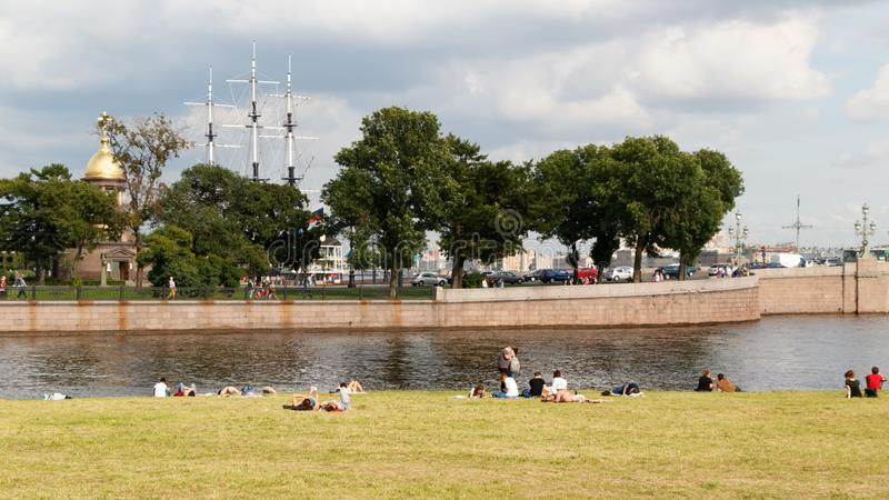SAINT PETERSBURG, RUSSIA - AUGUST 18, 2017: People resting on the banks of the Neva river at the Peter-Paul fortress royalty free stock photo