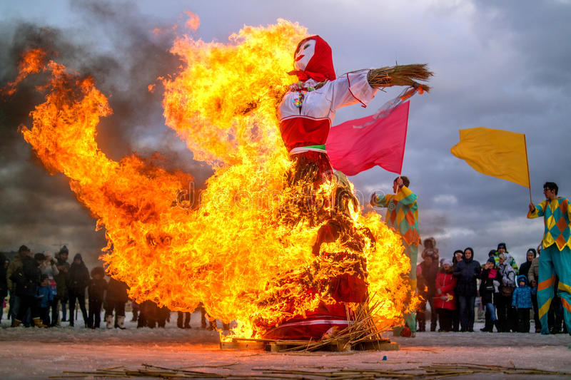 Saint-Petersburg, Russia - February 22, 2015: Feast Maslenitsa on Vasilyevsky Island. Burning doll - the flame is reflected on the snow. Spectators watch the stock photos