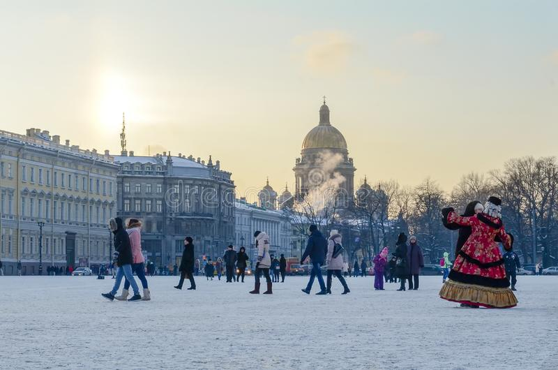 Saint Petersburg, Russia - 5, January 2016. People in historical costumes of the 18th century and walking tourists on the palace. Square on a frosty winter royalty free stock image