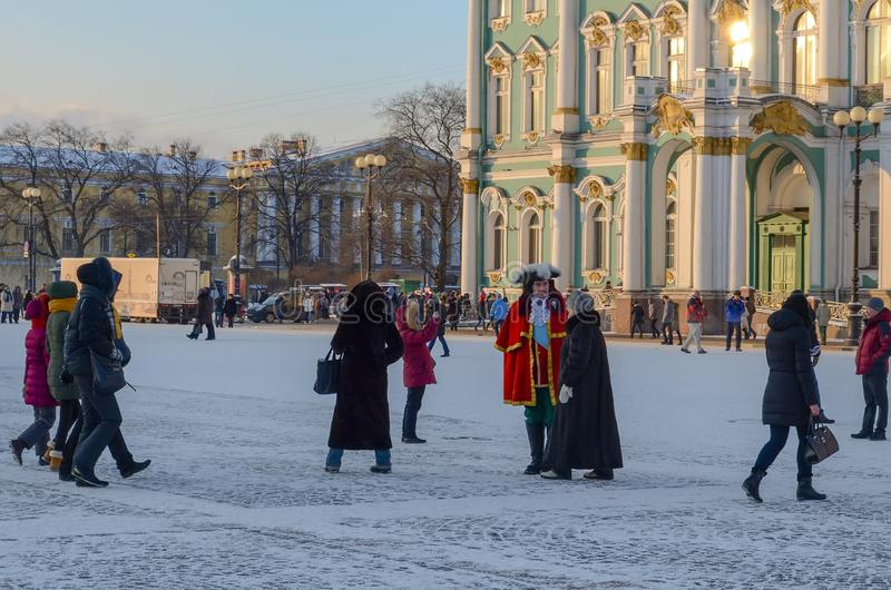 Saint Petersburg, Russia - 5, January 2016. People in historical costumes of the 18th century and walking tourists on the palace. Square on a frosty winter royalty free stock images