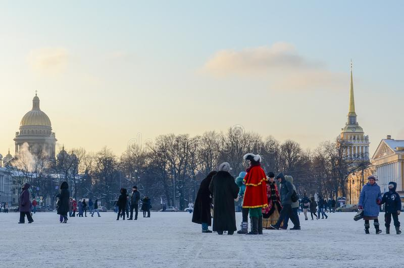 Saint Petersburg, Russia - 5, January 2016. People in historical costumes of the 18th century and walking tourists on the palace. Square on a frosty winter stock image