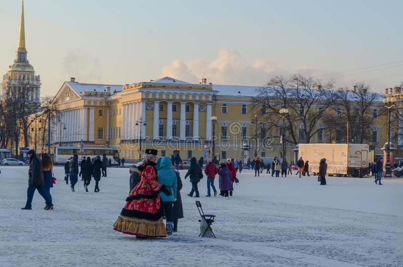 Saint Petersburg, Russia - 5, January 2016. People in historical costumes of the 18th century and walking tourists on the palace. Square on a frosty winter stock photography