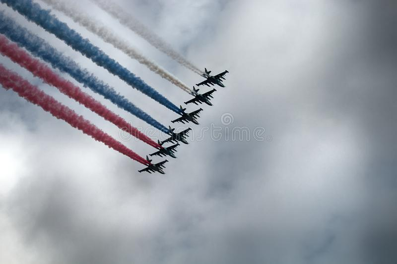 Russian attack aircraft SU-25, planes with colored contrail. Colors of Russian flag. Saint Petersburg, Russia - July 30, 2017: Su-25 aircraft NATO codification royalty free stock image