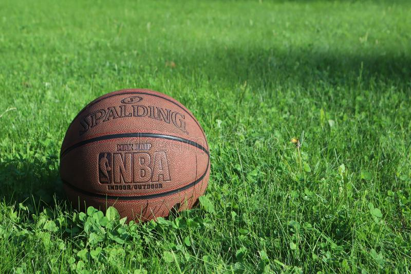 Saint Petersburg, Russia - JUNE 05 2019: basketball ball on green grass. concept of NBA playoff final. spalding basketball backgro. Und royalty free stock photos