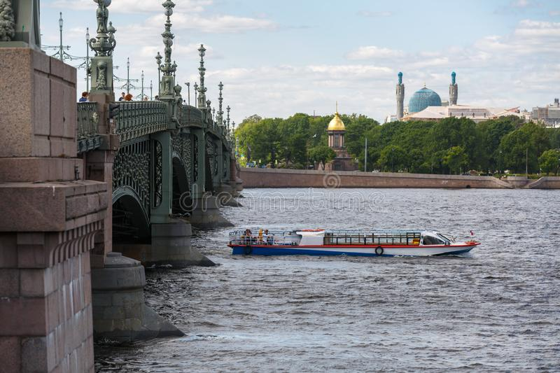 Small excursion ship just sailed under the Troitskiy Trinity Bridge on a spring sunny day. SAINT-PETERSBURG, RUSSIA, MAY 30, 2018: Small excursion ship just stock photo