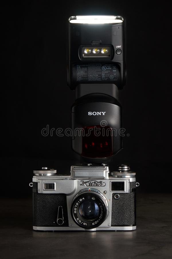 Saint-Petersburg / Russian Federation - February 8 2019: old camera Kiev with modern speedlight Sony on dark background. Saint-Petersburg / Russian Federation royalty free stock photography